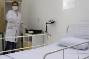 enfermeira paramentada em quarto isolado